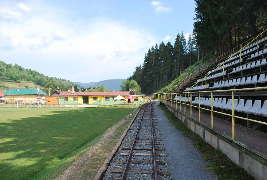 Čiernohronská železnica vedie cez futbalové ihrisko medzi tribúnou a trávnikom